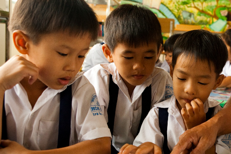 Schoolboys from Vietnam barely look up from what they're doing